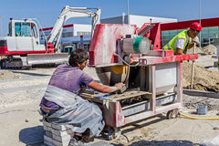 Il lavoratore con la sega circolare della lama del diamante sta tagliando pavimenta il bri di pietra Immagini Stock