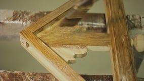 Il lavoratore con la spazzola vernicia un prodotto o una parte di legno di mobilia stock footage