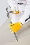 Il lavoratore con lo scalpello ed il martello controllano la base concreta Immagini Stock