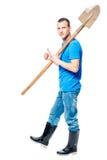 Il lavoratore con una pala va scavare su un bianco Fotografie Stock