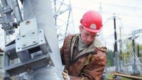 Il lavoratore controlla attentamente il tubo alzato con la gru video d archivio