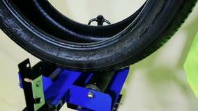 Il lavoratore controlla i segni ed il danneggiamento della gomma delle ruote e delle diagnosi stock footage