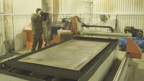 Il lavoratore controlla i vetri di protezione diretti per il taglio di metalli di un plasma a macchina stock footage