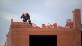 Il lavoratore costruisce la parete dei mattoni costruttore su costruzione che fa lavoro di muratura il costruttore al cantiere fa video d archivio