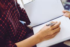 Il lavoratore creativo femminile del progettista sta scrivendo la nota sul notebo Fotografie Stock