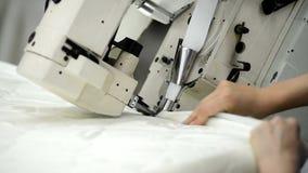 Il lavoratore cuce il panno sul materasso in fabbrica all'interno video d archivio