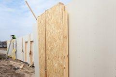 Il lavoratore del costruttore del Roofer con la gru che installa i pannelli isolati strutturali SORSEGGIA Casa di ottimo rendimen Fotografia Stock
