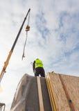 Il lavoratore del costruttore del Roofer con la gru che installa i pannelli isolati strutturali SORSEGGIA Casa di ottimo rendimen Immagini Stock Libere da Diritti