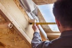 Il lavoratore del costruttore del Roofer con il righello installa la mansarda o la SK di plastica fotografia stock libera da diritti