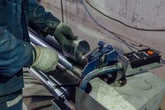 Il lavoratore del meccanico sta facendo le parti di collegamento per i tubi ed i tubi del metallo Fotografie Stock