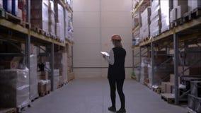 Il lavoratore dell'industria femminile in casco utilizza la compressa digitale mentre cammina fra le file degli scaffali di stocc video d archivio