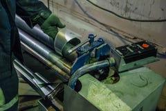 Il lavoratore dell'industria sta facendo le parti per i tubi ed i tubi del metallo Fotografie Stock Libere da Diritti