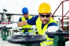 Il lavoratore dell'olio chiude la valvola sull'oleodotto immagini stock libere da diritti