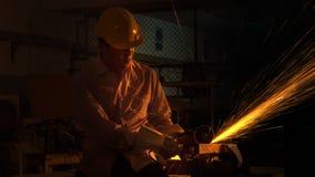 Il lavoratore dell'uomo usa la tagliatrice della macinazione per tagliare il metallo Fotografia Stock