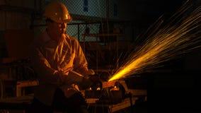 Il lavoratore dell'uomo usa la tagliatrice della macinazione per tagliare il metallo Immagine Stock