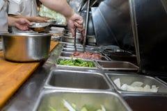 Il lavoratore della cucina prepara l'alimento Fotografie Stock