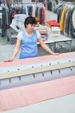 Il lavoratore della lavanderia della donna picchietta la tela sulla macchina automatica Immagine Stock