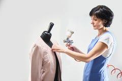 Il lavoratore della lavanderia della ragazza esegue i bomber della pittura su un manichino Immagini Stock Libere da Diritti