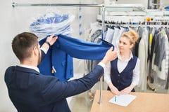 Il lavoratore della lavanderia della ragazza paga nelle mani Fotografie Stock Libere da Diritti
