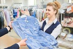 Il lavoratore della lavanderia della ragazza paga nelle mani dei vestiti puliti Fotografie Stock