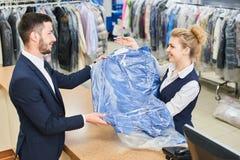 Il lavoratore della lavanderia della ragazza paga nelle mani dei vestiti puliti Fotografia Stock Libera da Diritti