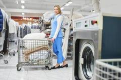 Il lavoratore della lavanderia della ragazza rotola un carretto con roba pulita Fotografia Stock Libera da Diritti