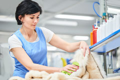 Il lavoratore della lavanderia della ragazza sta pulendo il cappotto con un panno Fotografie Stock