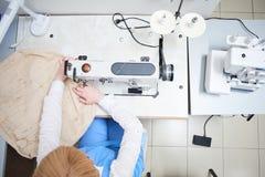 Il lavoratore della lavanderia esegue la riparazione di abbigliamento sulla macchina per cucire Fotografia Stock