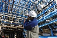 Il lavoratore della raffineria dentro il gigante canalizza le costruzioni fotografie stock