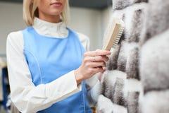 Il lavoratore della ragazza esegue la lavanderia asciutta, indumenti della pelliccia di pulizia della mano Immagini Stock Libere da Diritti