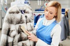 Il lavoratore della ragazza esegue la lavanderia asciutta, indumenti della pelliccia di pulizia della mano Immagini Stock