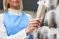 Il lavoratore della ragazza esegue la lavanderia asciutta, indumenti della pelliccia di pulizia della mano Immagine Stock Libera da Diritti