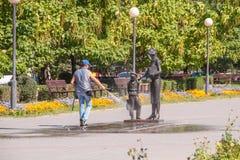 Il lavoratore di alloggio e di servizi comunali lava con acqua dal monumento del tubo flessibile al primo insegnante Volgograd immagine stock