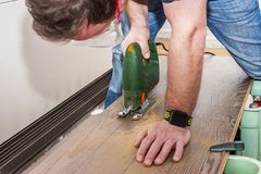 Il lavoratore di DIY che taglia il pannello di legno con la maschera ha visto Immagine Stock Libera da Diritti