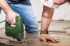 Il lavoratore di DIY che taglia il pannello di legno con la maschera ha visto Immagini Stock
