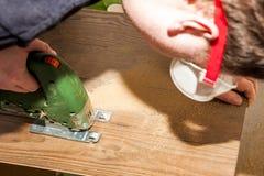 Il lavoratore di DIY che taglia il pannello di legno con la maschera ha visto Fotografia Stock