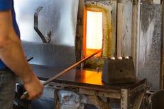 Il lavoratore di fabbricazione riscalda il vetro in forno per il riscaldamento del vetro immagine stock