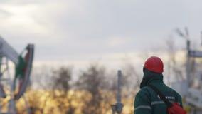 Il lavoratore di vista laterale del movimento lento cammina lungo il giacimento di petrolio dell'inverno archivi video