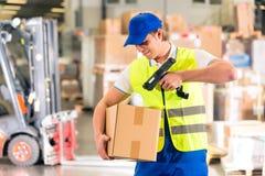 Il lavoratore esplora il pacchetto in magazzino di spedizione Fotografia Stock