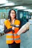 Il lavoratore esplora il pacchetto in magazzino di spedizione Immagini Stock