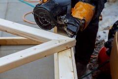 Il lavoratore fa gli impianti di rifinitura delle pareti con un bordo di legno bianco, facendo uso della linea livello del laser Immagini Stock Libere da Diritti