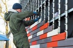 Il lavoratore fa il rivestimento ed il riscaldamento della parete da una pietra decorativa artificiale fotografia stock libera da diritti