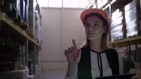 Il lavoratore femminile sveglio del magazzino con la compressa digitale a disposizione fa l'inventario e conta le scatole stock footage
