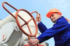 Il lavoratore gira la grande valvola a gas Fotografie Stock