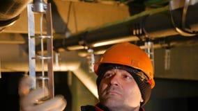 Il lavoratore gira in tondo la parte sul tubo della pianta in officina stock footage
