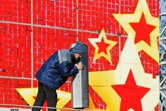Il lavoratore installa gli altoparlanti su un fondo festivo rosso con le stelle sulla via a Volgograd Fotografia Stock Libera da Diritti