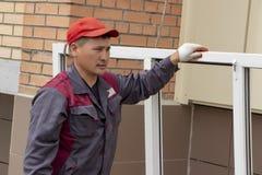 Il lavoratore installa la finestra degli aumenti delle finestre l'alto pavimento immagini stock