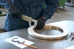 Il lavoratore, l'ingegnere misura la parte, l'anello brillante del metallo, la flangia con un calibro sulla tavola di lavoro del  Fotografia Stock