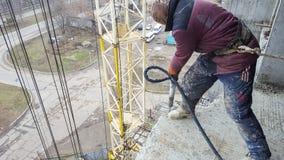 Il lavoratore lavora al cantiere con un martello pneumatico pneumatico immagine stock