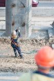 Il lavoratore livella la misura del piatto che solleva dalla gru Fotografia Stock